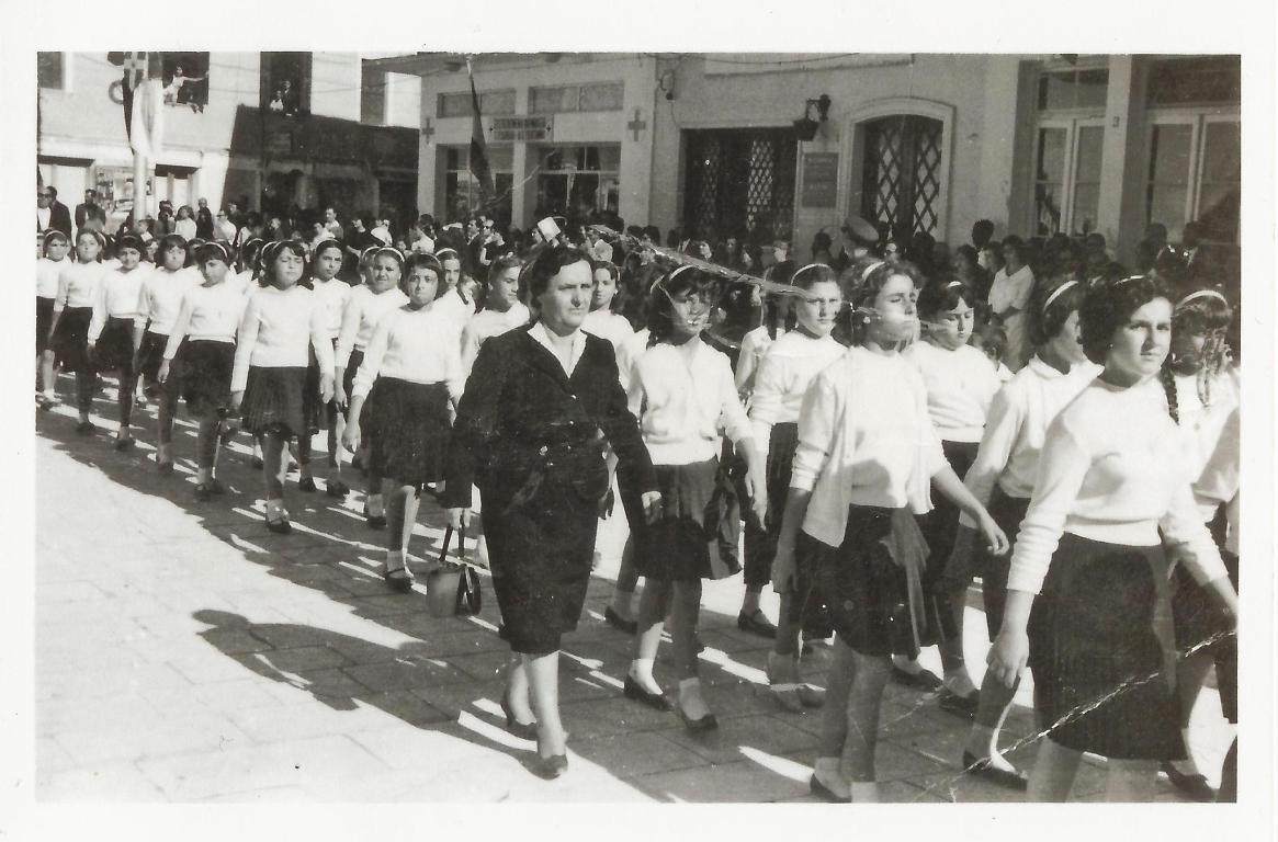 25 Μαρτίου 1960: Παρέλαση στην Κεντρική Πλατεία. Το γωνιακό κτίριο ήταν τότε το Φαρμακείο Καββαδά (σήμερα στεγάζεται το καφέ του «Τζορέλου»), και δίπλα ακριβώς στεγαζόταν η Εθνική τράπεζα. Παρελαύνουν οι Ε΄ η ΣΤ ΄ τάξεις του Δημοτικού σχολείου. Δασκάλα είναι η Γεωργία Σκλαβενίτη. Εικονίζονται οι μαθήτριες: Αρετή Βούλγαρη, Ελένη Ματαράγκα, Φιλίτσα Ορφανού, Παρασκευή Ροντογιάννη, Γεωργία Κατωπόδη, Μάχη Μεσσήνη, Βούλα Σβορώνου, Ευλαμπία Μαυροκέφαλου, Αγγελική Βαγενά.