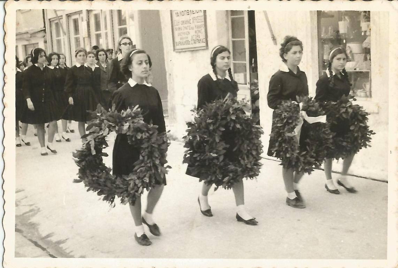 25 Μαρτίου 1964. Οι μαθήτριες διασχίζοντας την κεντρική αγορά κατευθύνονται στο Ηρώον. Βρισκόταν στο χώρο που υπάρχει σήμερα ο φοίνικας, μπροστά από το καφέ «Μποσκέτο». Τα κορίτσια με τα στεφάνια στο χέρι βρίσκονται στο σημείο που είναι σήμερα το ξενοδοχείο «Πυροφάνι». Τότε σ' αυτό το σημείο ήταν το υαλοπωλείο «Σταύρακα» και τα σαλάμια «Ντελεμάρη».