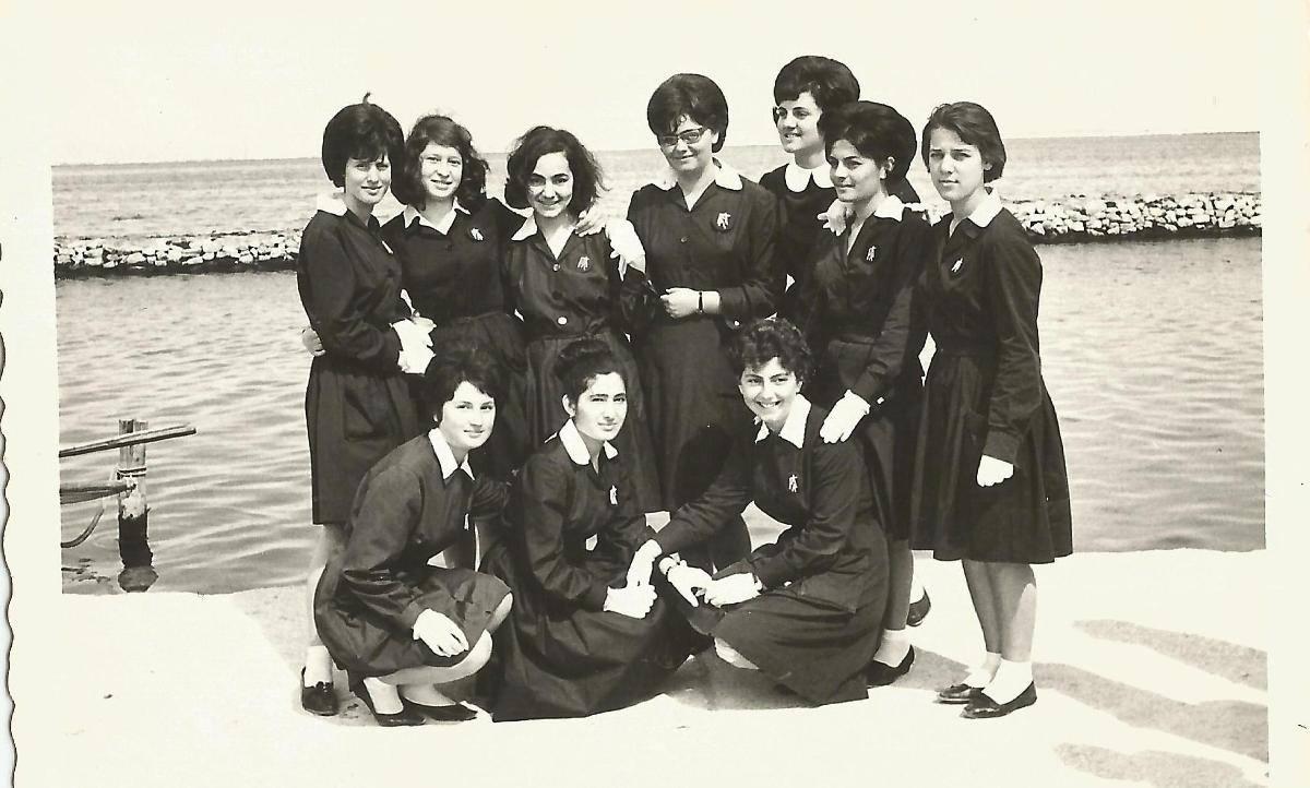 25 Μαρτίου 1965. Μόλις έχει δημιουργηθεί το «Πρακτικό» σχολείο. Τα 10 πρώτα και τολμηρά κορίτσια των θετικών επιστημών παρελαύνουν σε ξεχωριστό τμήμα για πρώτη φορά μαζί με το Λύκειο Αρρένων. Μετά την παρέλαση φωτογραφήθηκαν από τον φωτογράφο Μ. Ιασωνίδη στην παραλία. Η φορεσιές της παρέλασης για τα κορίτσια ήταν μπλε ποδιά φρεσκοσιδερωμένη με άσπρο γιακαδάκι. Εικονίζονται: Μαρία Καββαδά, Ευγενία Κουκουλιώτη, Ειρήνη Τσαντιώτη, Σοφία Αρματά, Γεωργία Βλάχου, Ζωή Κατωπόδη, Βούλα Σβορώνου, Αγγελική Παπαδάτου, Ελένη Κακλαμάνη, Ελένη Ματαράγκα.