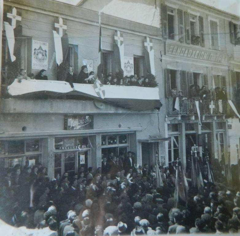25 Μαρτίου 1950. Οι εορταστικές εκδηλώσεις πραγματοποιούνται στην Κεντρική Πλατεία της Λευκάδας. Στη φωτογραφία εικονίζεται το Δημαρχείο. Ομιλητής ο παπά Νίκος Ματαράγκας (δάσκαλος).Το Δημαρχείο στεγαζόταν τότε στον πάνω όροφο του κτιρίου που βρίσκεται δίπλα από το ξενοδοχείο «Πάτραι» στην κεντρική πλατεία. Στο ισόγειο του κτιρίου ήταν το κέντρο διασκέδασης «Κομπίτσης».