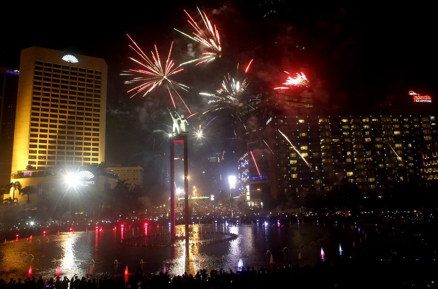 epa05084677 Residents watch fireworks at Jakarta's main roundabout in Indonesia, 31 December 2015, during new year's eve celebration. EPA/ADI WEDA