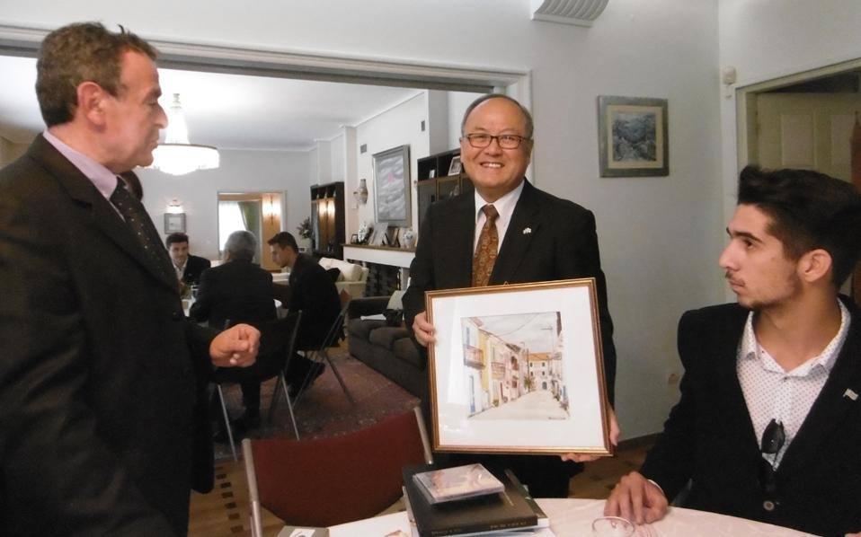 Περιχαρής με το δώρο του –με τον ωραίο πίνακα ζωγραφικής της Λευκάδος από την κ. Βούλα Ράπτη– ο πρέσβης της Ιαπωνίας, κ. Masuo Nishibayashi.